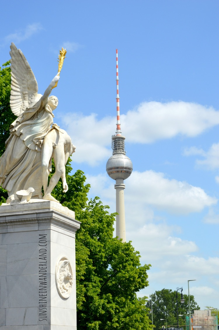 view over the fernsehturm and stone figures monuement berlin by bike on a budget